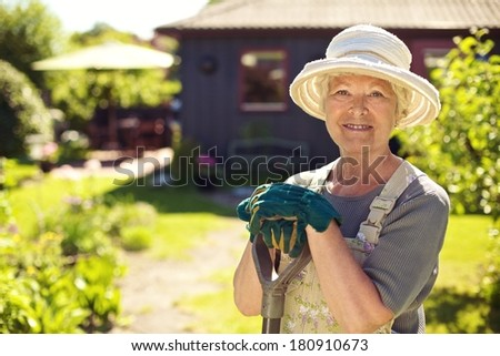Portrait of senior woman wearing hat with gardening tools outdoors. Elder woman standing with shovel in her backyard garden - stock photo