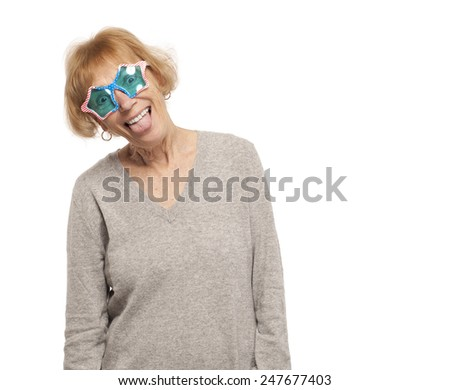 Portrait of senior woman wearing star shape glasses and sticking out tongue - stock photo