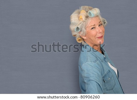 Portrait of senior woman with hair curlers - stock photo