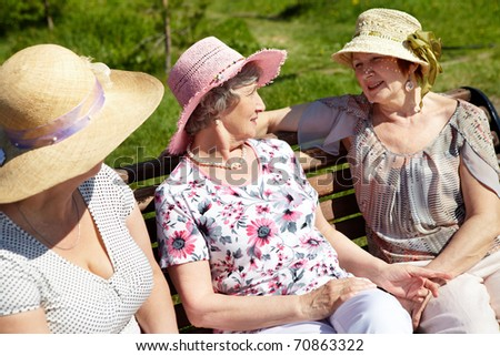 Portrait of senior women sitting on the bench in open air - stock photo