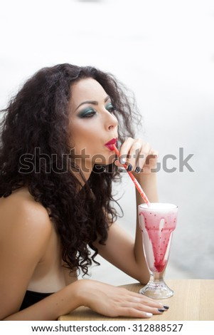 Portrait of sensual attractive cute young woman with curly brown hair and fashion bright makeup looking away sipping cocktail through straw on white background isolated, vertical picture - stock photo