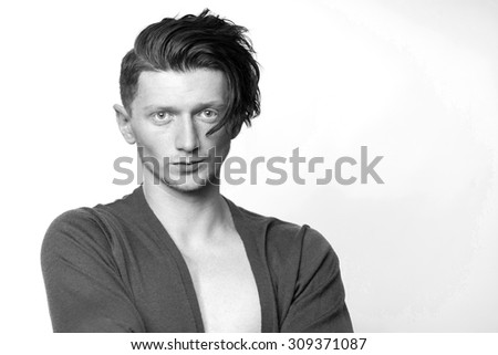 Portrait of sensual attractive young boy model with stylish hairdo in jersey looking forward standing in studio on white background copyspace, horizontal picture - stock photo