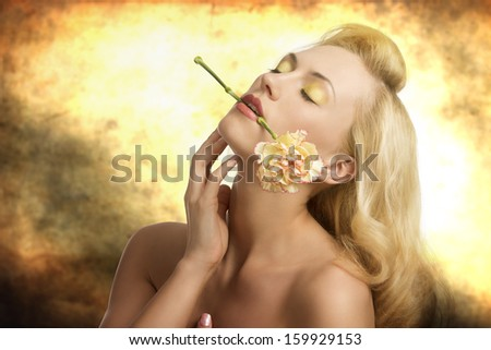 portrait of sensual blonde girl with long hair, colorful make-up and naked shoulders in alluring pose with carnation in her mouth  - stock photo