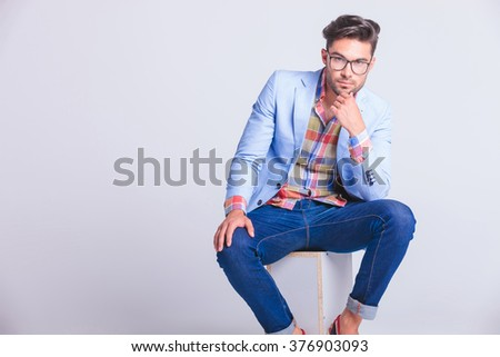 portrait of sensual casual man wearing glasses and jeans seated and thinking while looking at the camera in studio background - stock photo