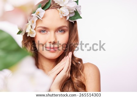 Portrait of sensual girl in floral wreath looking at camera - stock photo