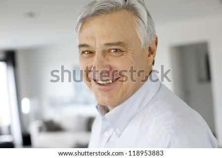 Portrait of serene senior man looking at camera - stock photo