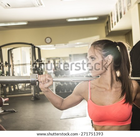 portrait of serious athlete girl holds metal barbell. Trim and beautiful woman in sportswear is training inside gym. Female raises the bar Empty space for inscription against mirror reflection  - stock photo