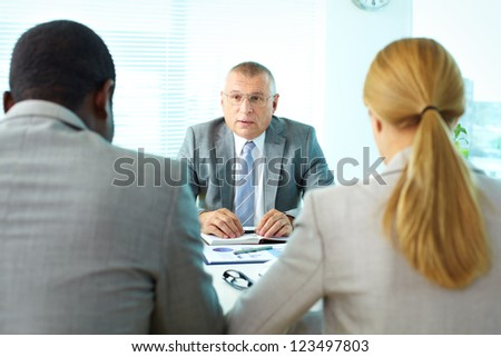 Portrait of serious boss interacting with his employees - stock photo