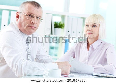 Portrait of serious boss looking at camera at workplace with mature woman looking at him on background - stock photo