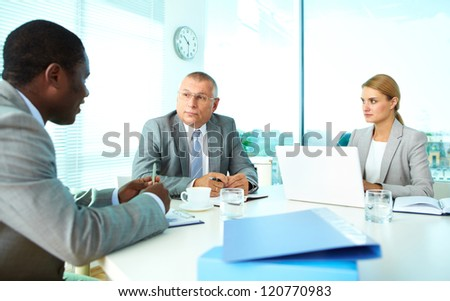 Portrait of serious boss looking at his employee with pretty secretary near by - stock photo