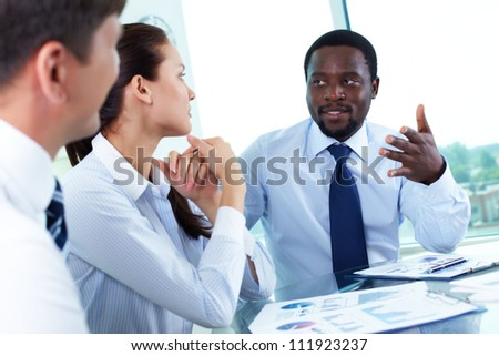 Portrait of serious boss talking to his employees at meeting - stock photo