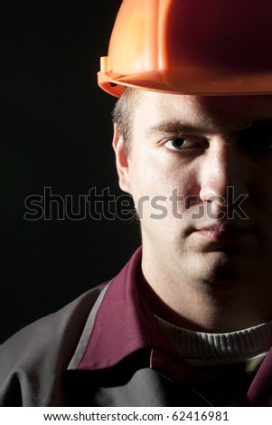 Portrait of serious builder in workwear and helmet - stock photo