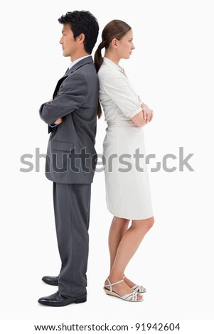 Portrait of serious business people standing back to back against a white background - stock photo