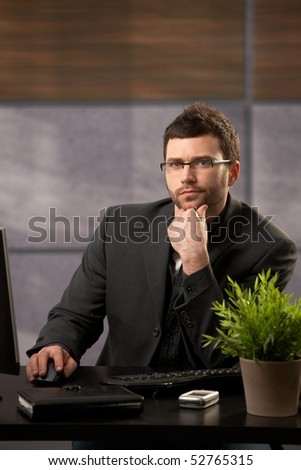 Portrait of serious businessman looking at camera, sitting at desk in office. - stock photo