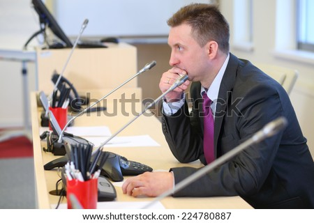 Portrait of serious businessman with a microphone in his workplace  - stock photo