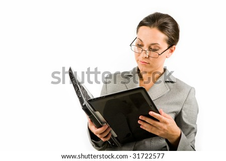 Portrait of serious businesswoman with laptop reading information from its display - stock photo