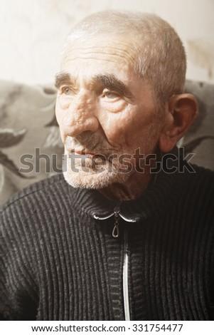 Portrait of serious caucasian senior man looking sideways - stock photo