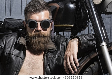 Portrait of serious confident handsome sexy unshaven man with beard and handlebar moustache in leather biker jacket with bare torso and aviator sunglasses sitting near motorcycle, horizontal picture - stock photo