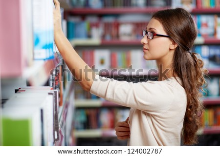 Portrait of serious girl in library looking for a book - stock photo