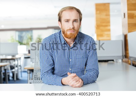Portrait of serious handsome bearded businessman sitting at the table in office - stock photo