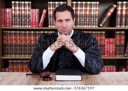 Portrait of serious judge thinking while sitting at desk in courtroom - stock photo