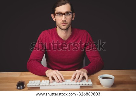 Portrait of serious man typing on keyboard with coffee on desk in office - stock photo