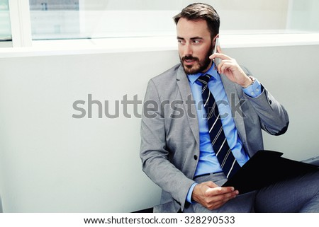 Portrait of serious purposeful man bookkeeper talking on mobile phone while sitting with paper documents in office interior, handsome male manager in suit speaking on cell telephone during work break - stock photo