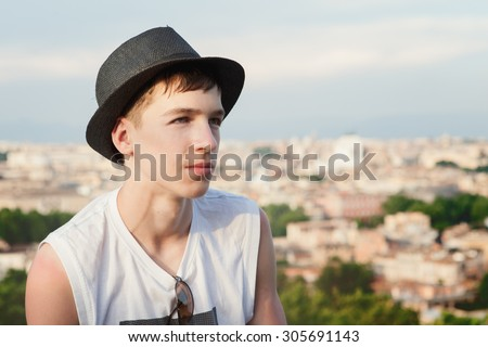 Portrait of serious thoughtful teenager on  background of city , boy wearing black hat - stock photo