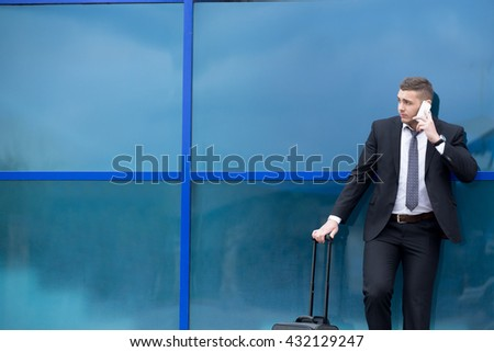 Portrait of serious young man on business trip standing with his luggage while talking on smartphone in front of modern glass building outdoors. Travelling guy making call. Copy space - stock photo