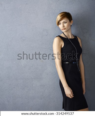 Portrait of serious young woman in black dress leaning to wall - stock photo