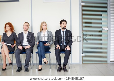 Portrait of several business associates sitting on chairs by office door - stock photo