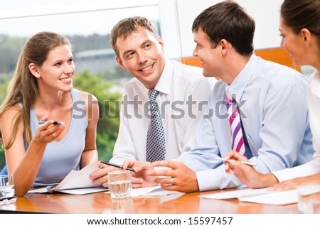 Portrait of several business people sitting in office and discussing new plans and ideas - stock photo