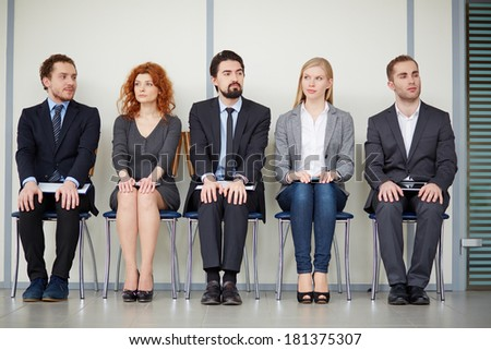 Portrait of several elegant employees sitting on chairs - stock photo