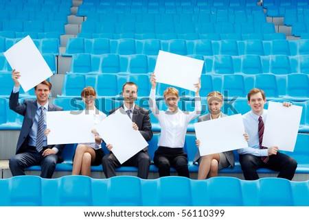 Portrait of several successful partners with blank papers sitting on stadium and looking at camera - stock photo