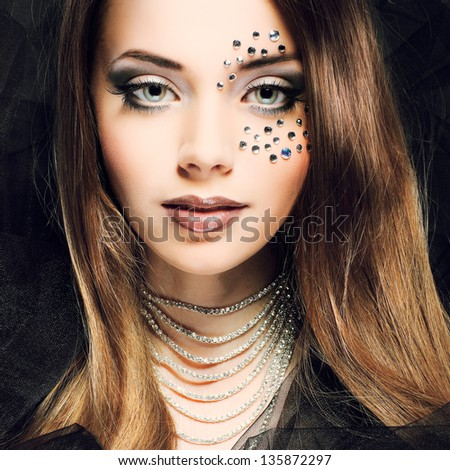 Portrait of sexual beautiful girl with strasses on face, on a dark-grey background - stock photo