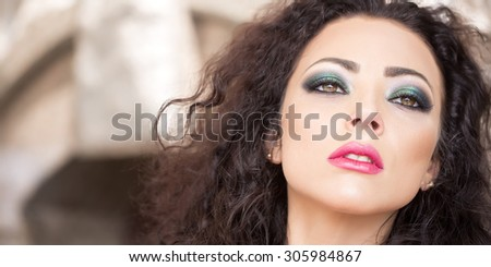 Portrait of sexual pretty young brunette woman with curly hair bright makeup expressive green brown eyes and pink lips looking forward sitting outdoor, horizontal picture - stock photo
