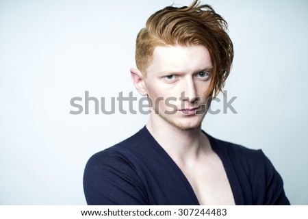 Portrait of sexy attractive young man model with red hair in black jersey looking forward standing in studio on white background copyspace, horizontal picture - stock photo