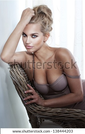Portrait of sexy beautiful blonde woman wearing lingerie, sitting on wicker chair. - stock photo