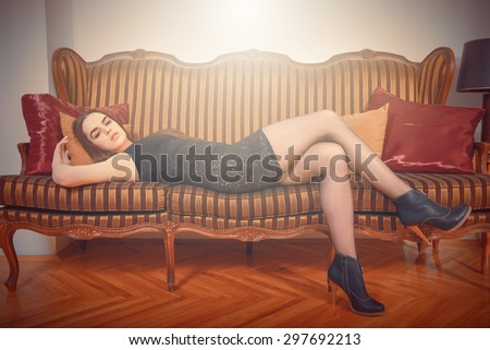 Portrait of sexy beautiful woman lying in long heels on sofa. Luxurious female model in seductive dress posing on retro couch. Attractive fashion person in vintage interior.Naughty girl, haze effect. - stock photo