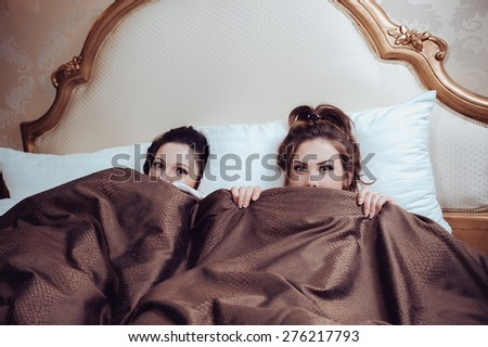Portrait of sexy beautiful young ladies in bed and looking at camera - stock photo
