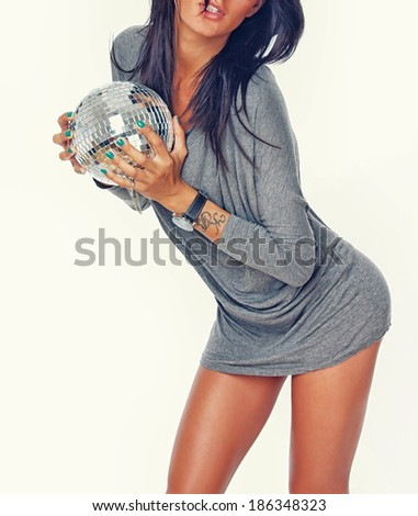 Portrait of sexy brunet posing in studio with discoball - stock photo
