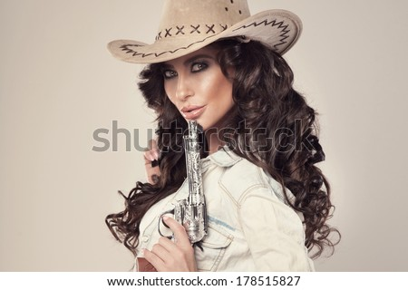 Portrait of sexy brunette cowgirl with revolver, looking at camera. - stock photo