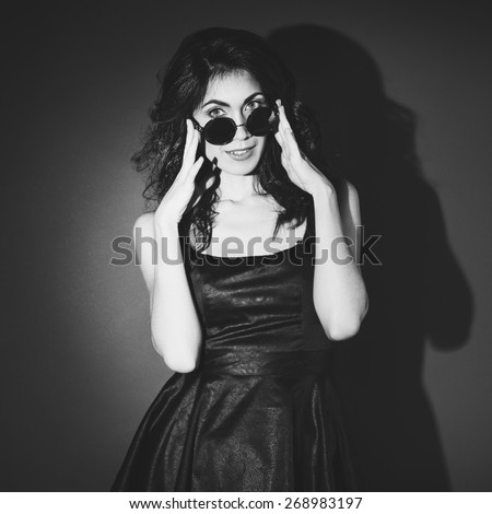 Portrait of sexy brunette woman in black dress with round glasses - stock photo