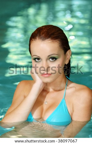 portrait of sexy brunette woman in swimming pool - stock photo