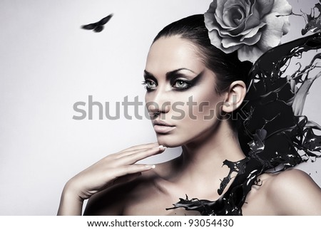portrait of sexy brunette woman with black splash and rose - stock photo