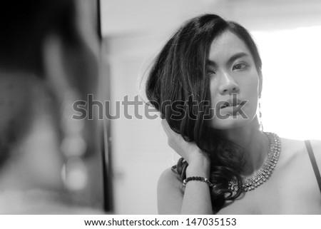 Portrait of sexy brunette woman with mirror, black and white photo - stock photo
