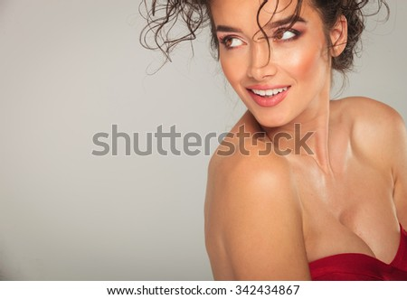 portrait of sexy busty woman in red dress side posing for the camera - stock photo