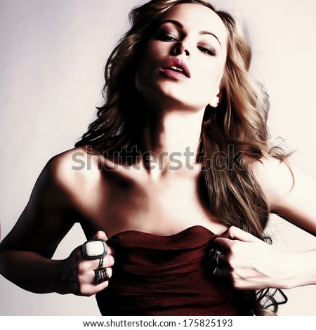 portrait of sexy caucasian young woman in red dress with long blond hair, beautiful eyes, sensual lips and clean skin - stock photo