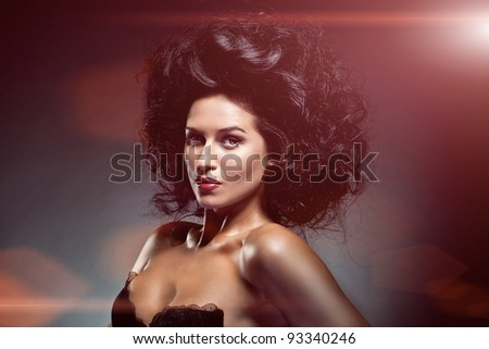Portrait of sexy caucasian young woman with beautiful black hair posing on dark background - stock photo