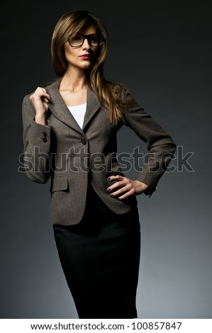 Portrait of sexy elegant woman wearing suit and glasses isolated on dark background fashion photo - stock photo